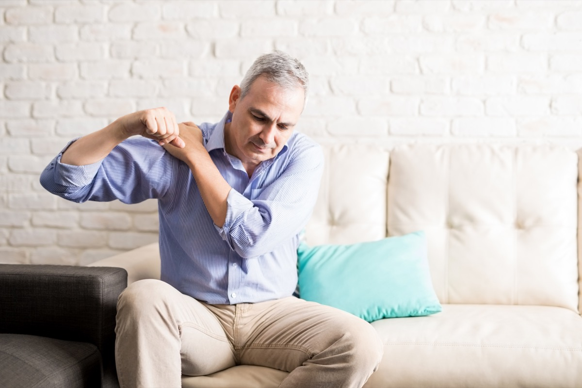 Middle aged man sitting on the sofa and holding painful shoulder with another hand.