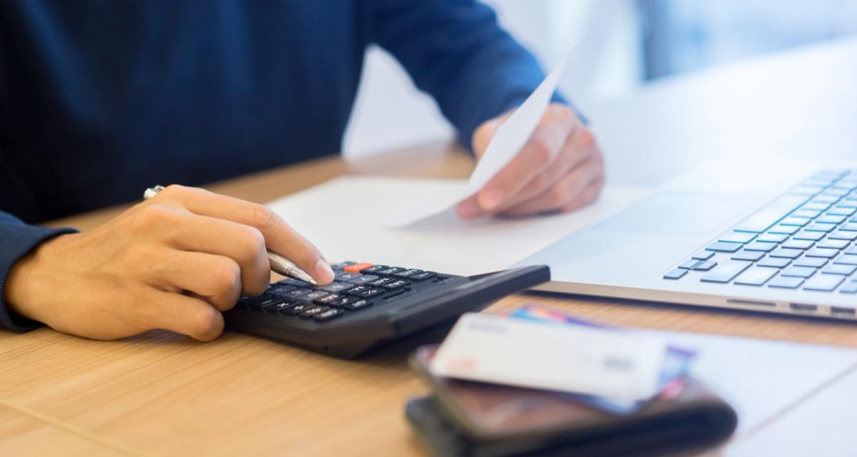 man using calculator to pay bills