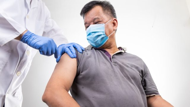 middle age man with face mask receiving Covid-19 vaccine injection onto the arm by medical practitioner