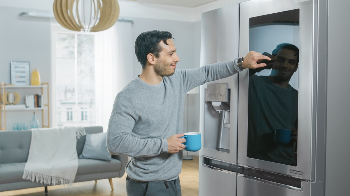young man touching smart appliance, refrigerator, holding coffee cup