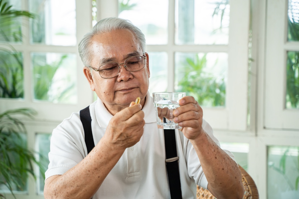 man with cup of water and pill looking at camera and taking remedy in cozy room at home. Old male taking medicine.