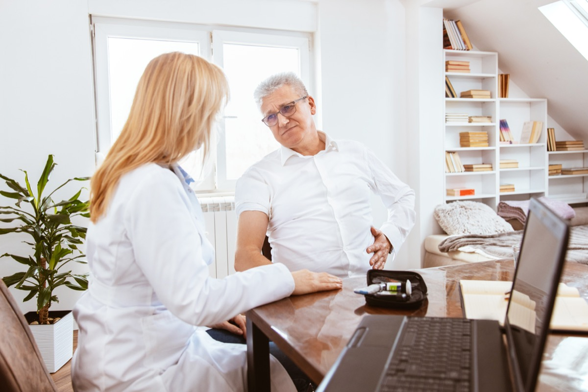 Middle-aged man being examined by a female doctor in a doctor's office. Patient complains to the doctor of pancreas pain.