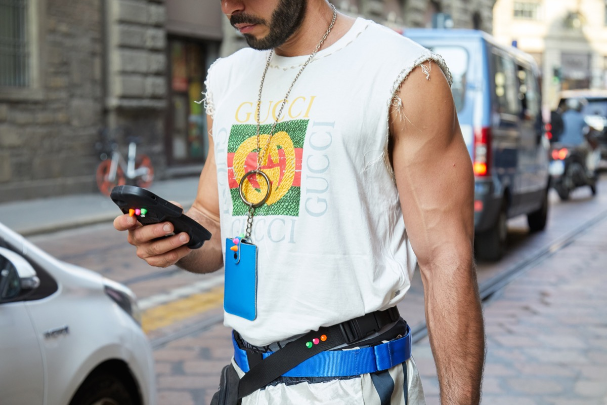 MILAN, ITALY - SEPTEMBER 20, 2018: Man with torn Gucci shirt looking at smartphone before Vivetta fashion show, Milan Fashion Week street style