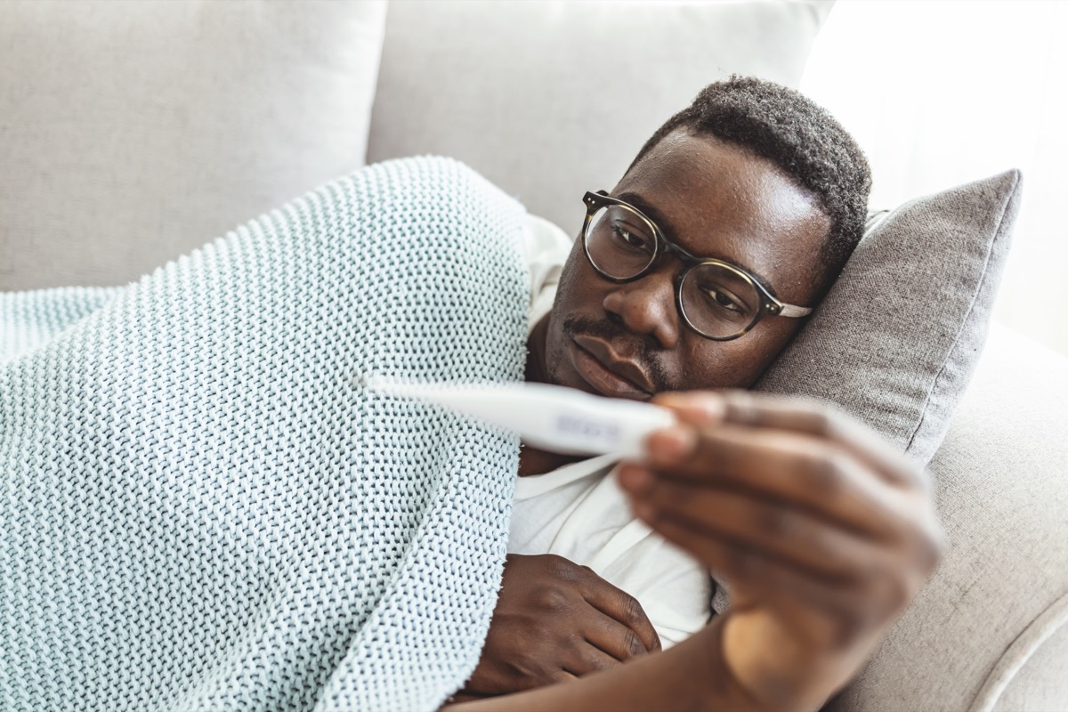 Shot of a young man checking his temperature while lying on the couch at home