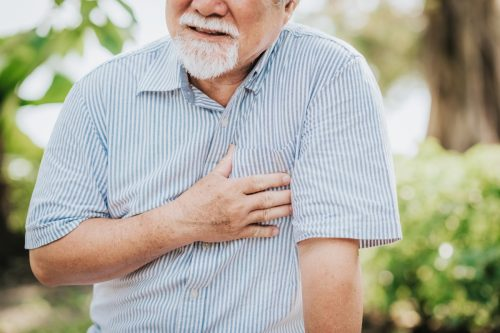 Cropped shot of senior man holding his chest and feeling pain suffering from heart attack outdoor at the park