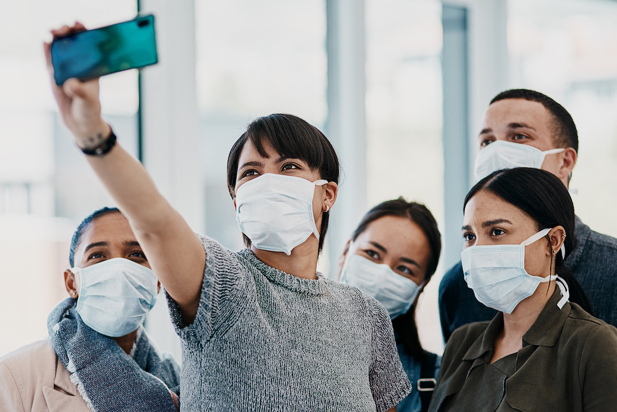 Shot of a group of young people wearing masks and taking selfies at the airport