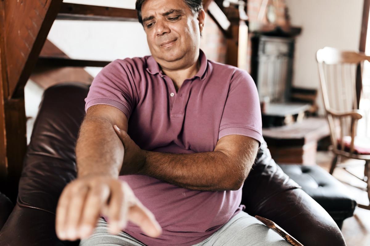Man feeling elbow pain, sport injury, chronic rheumatism, health problem