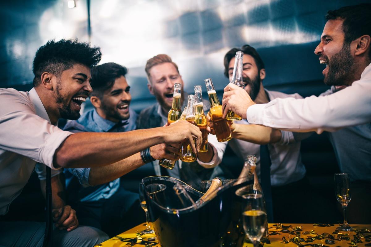 men toasting at a nightclub, drinking beer