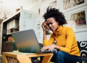 female freelancer working from home using her laptop and encountering some problems concerning her business
