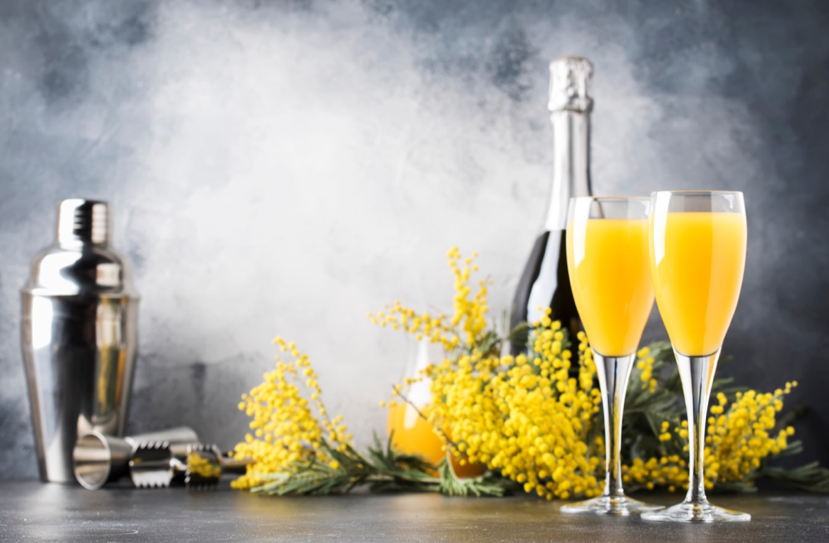 glasses of mimosa near champagne bottle