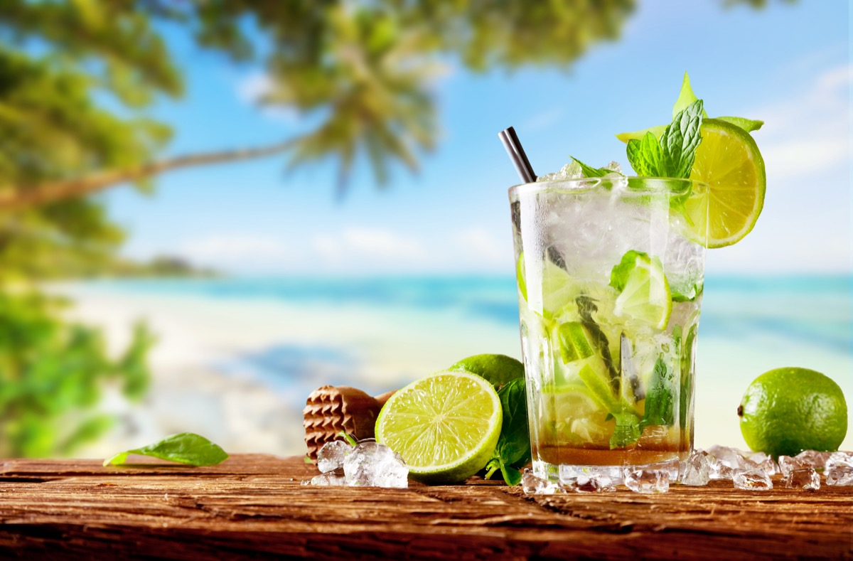 mojito in glass on wooden plank near beach
