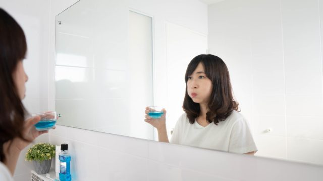 woman rinsing and gargling mouth with mouthwash after brushing her teeth in bathroom.