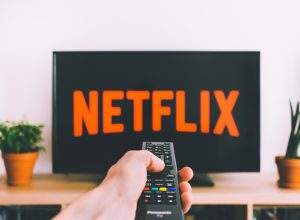 A person pointing a remote control at a TV with the Netflix logo on it