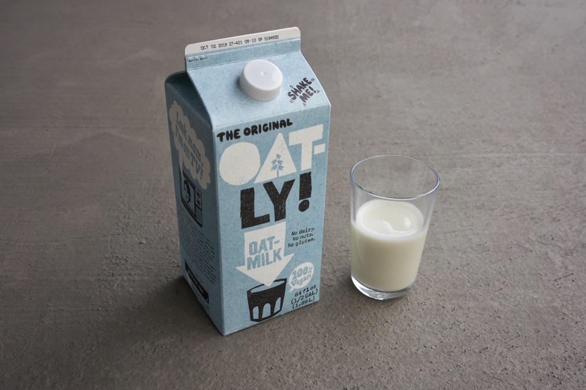 oatly oat milk, light blue milk carton, glass of milk