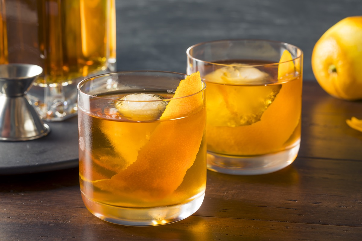 old fashioned cocktail with fruit peel and large ice cubes