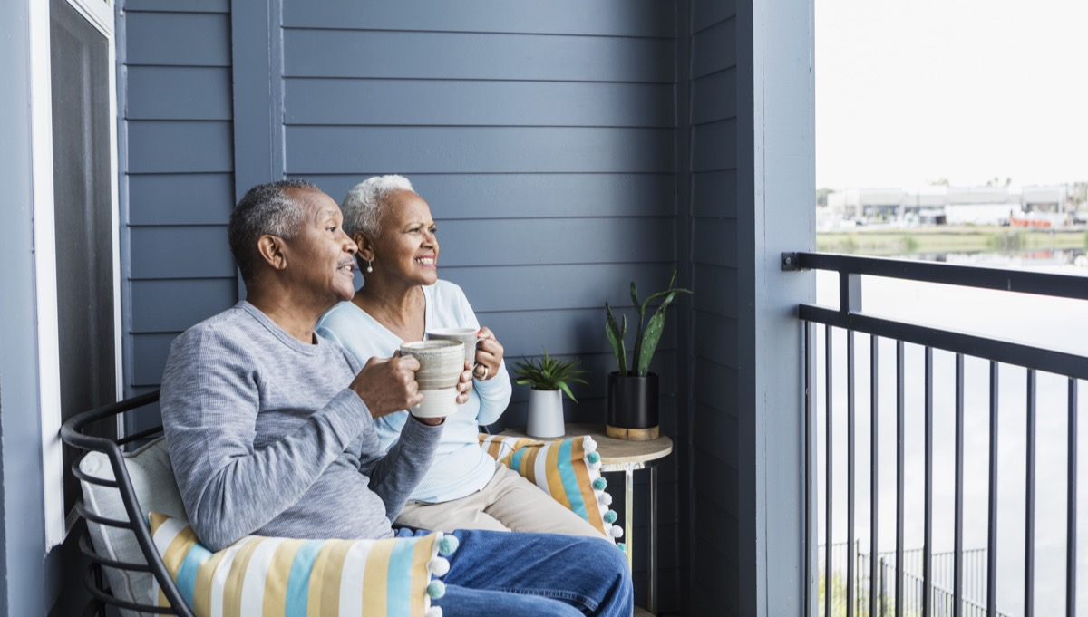couple sitting side by side on their porch or balcony, drinking coffee. They are looking at something in the distance, squinting to try to figure out what it is.