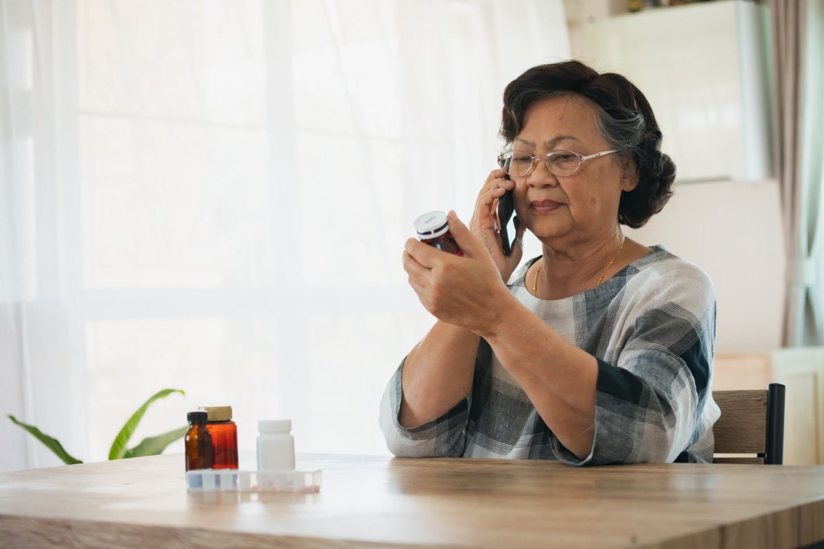 older woman making phone call while looking at pill bottle