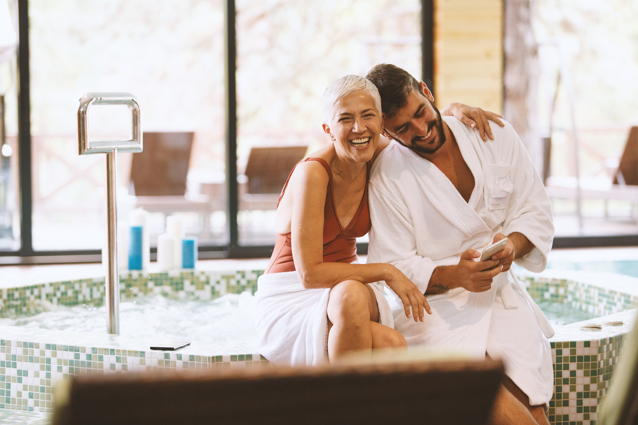 A mature woman and younger man hug while spending time at a spa