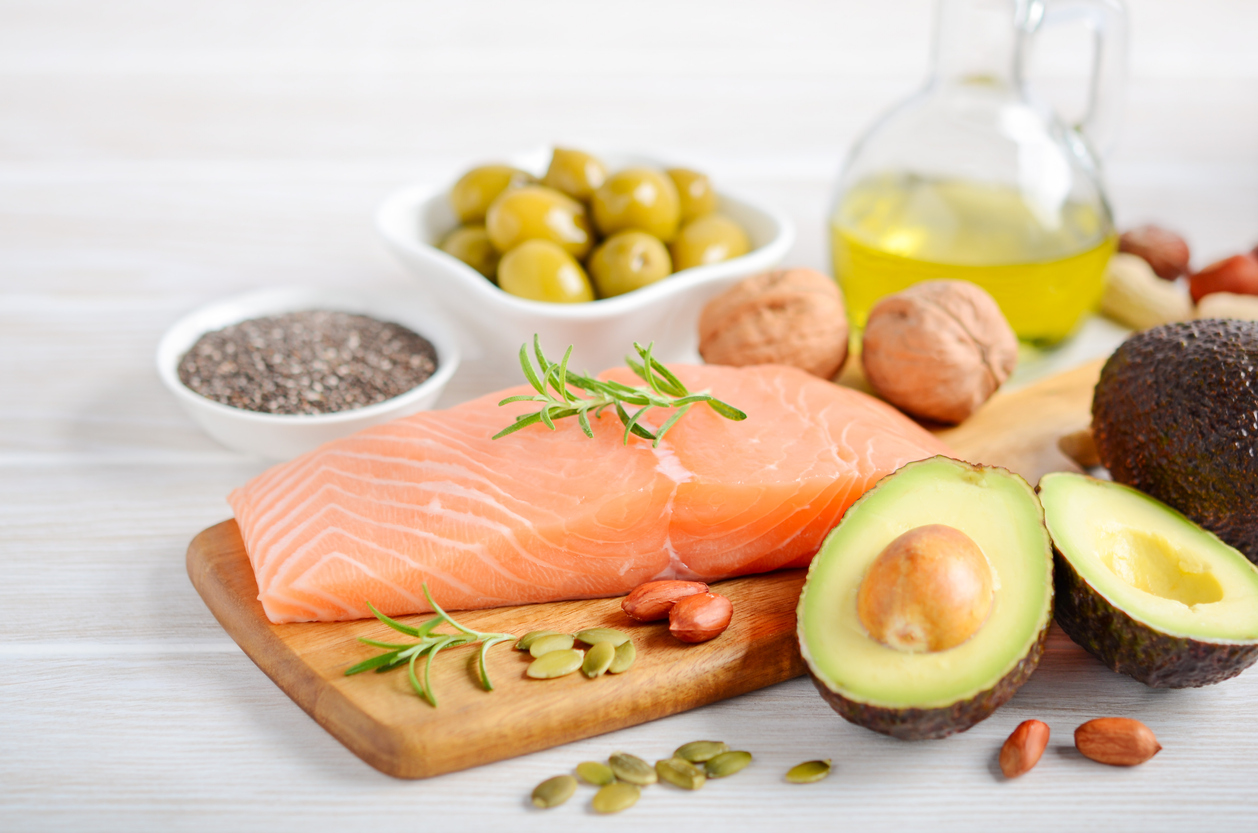 Salmon, avocados, olives, and nuts sitting on a board