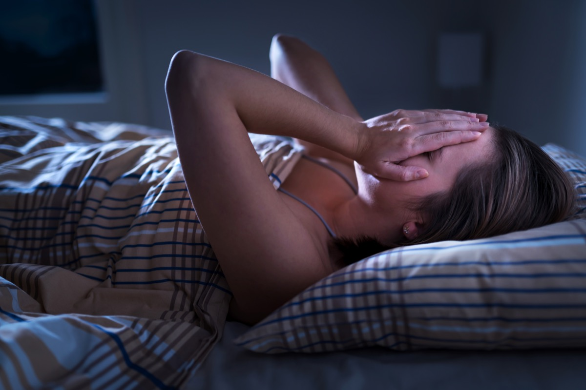 Insomnia, sleep apnea or stress concept. Sleepless woman awake and covering face in the middle of the night. Lady can't sleep. Nightmares or depression. Suffering from headache or migraine.
