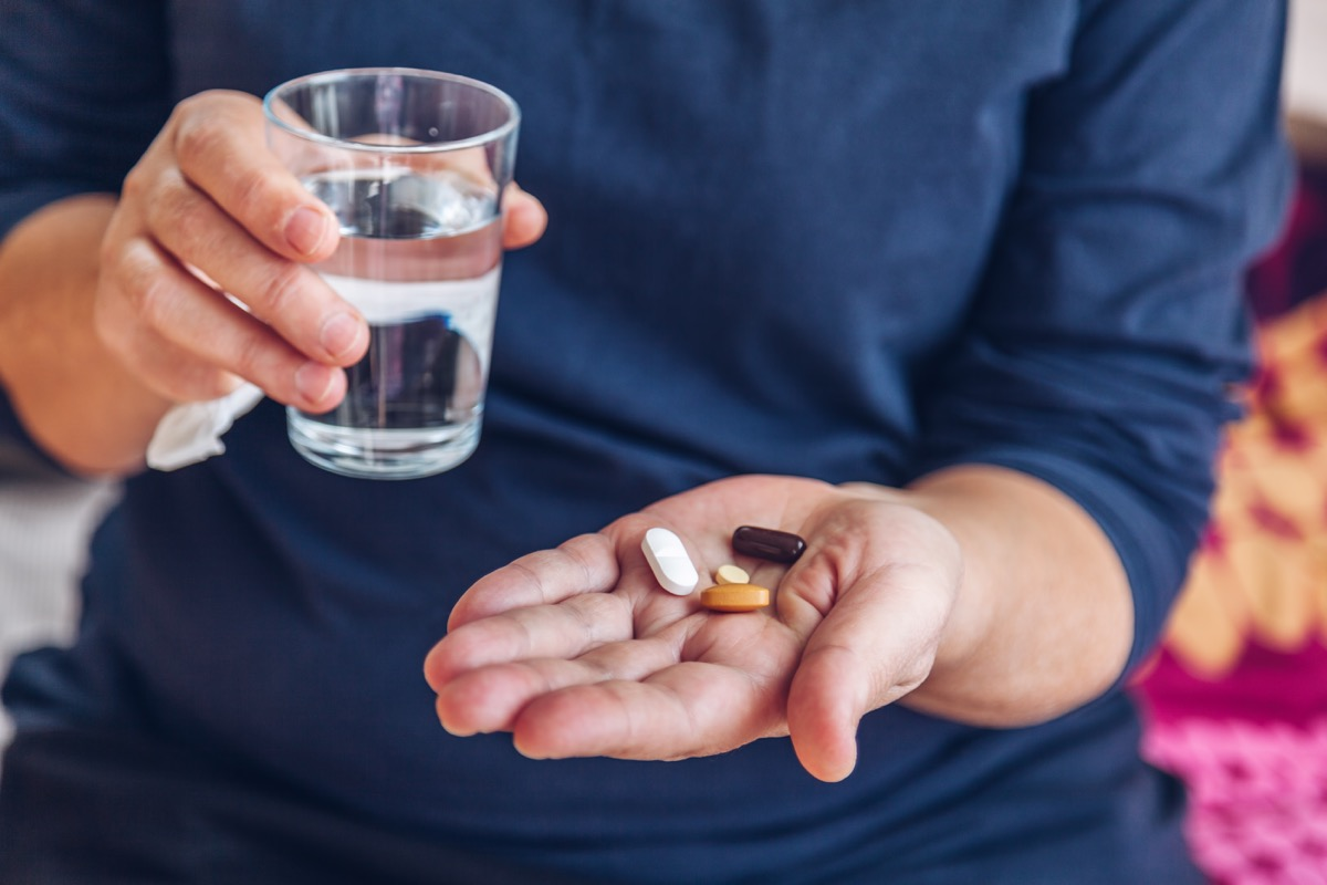 Senior woman holding medical pills and a glass of water on the bed