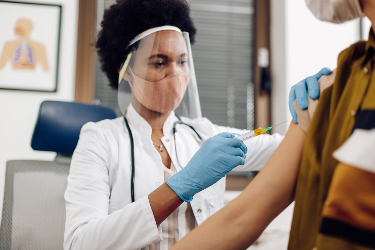 female doctor giving a Covid-19 vaccine to a young woman.