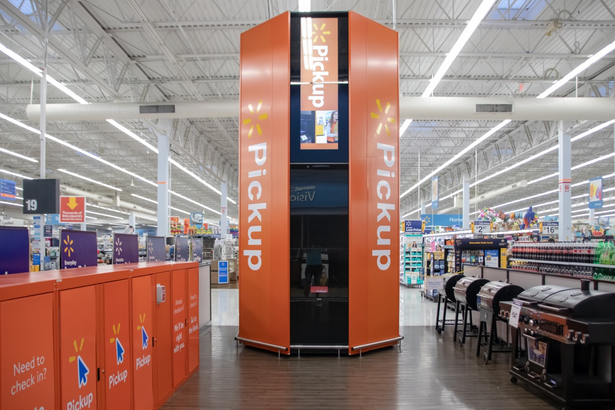 Coral Springs, Florida/USA - June 22, 2019: Walmart Supercenter Pickup Area in modern style and orange color. Young boy pick up his order, package with pets crate.