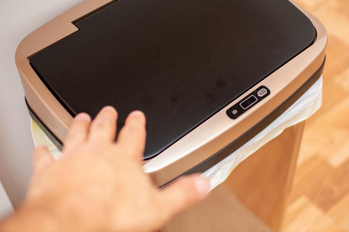 hand reaching toward sensor trash can