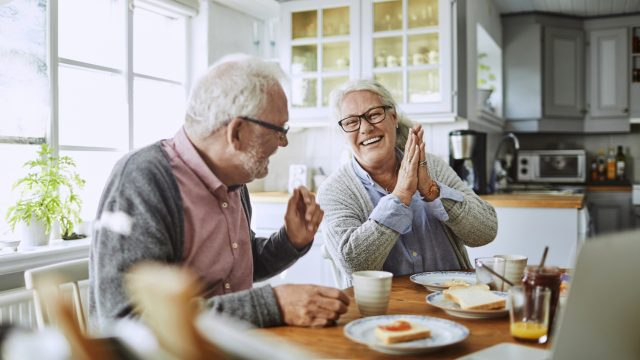 A senior couple eating breakfast and smiling