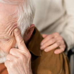 A senior man sits in a wheel chair with a concerned look on his face