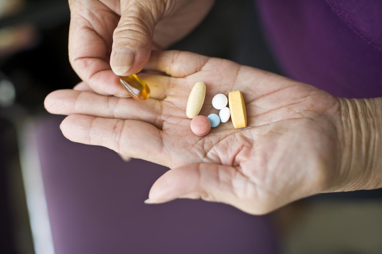 A senior person's hands holding supplement pills