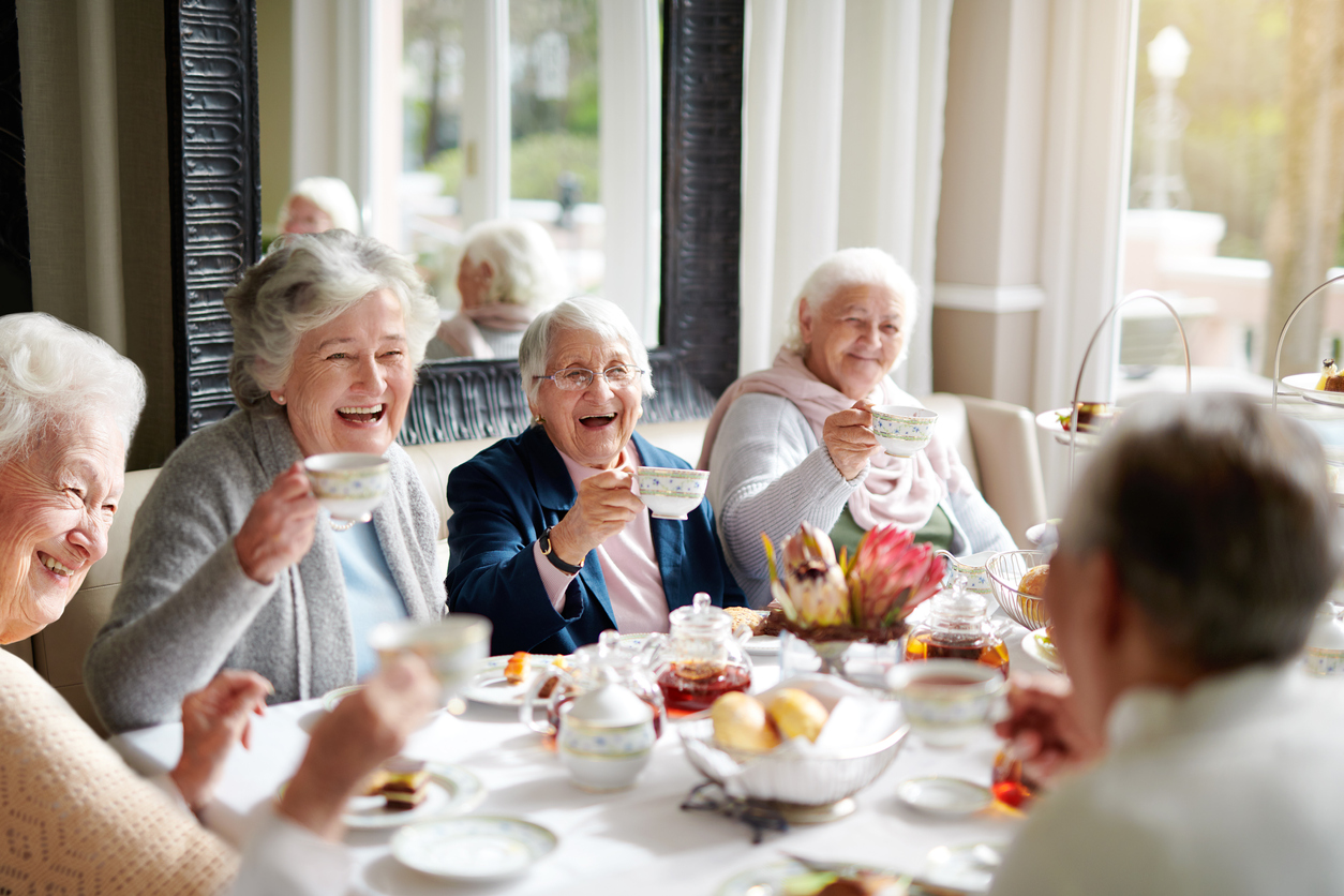 Group of senior women sitting around a table eating and drinking tea, smiling