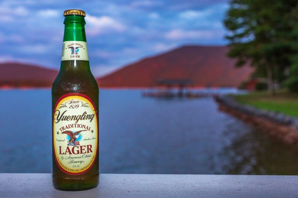 yuengling beer bottle near a lake