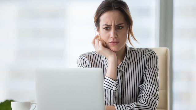 woman looking at laptop, worried look on face