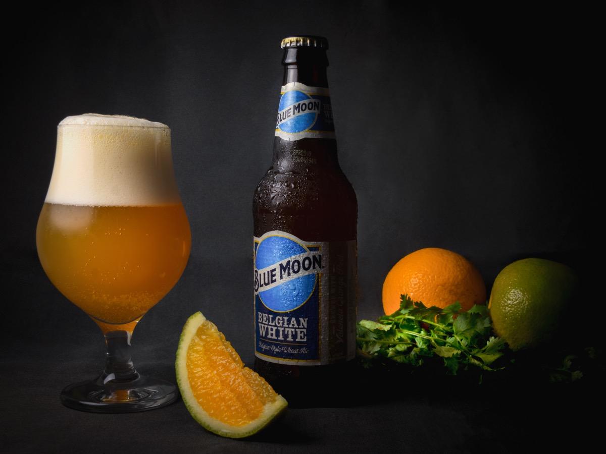 bottle of blue moon next to orange, glass
