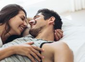 young couple smiling at each other under the sheets