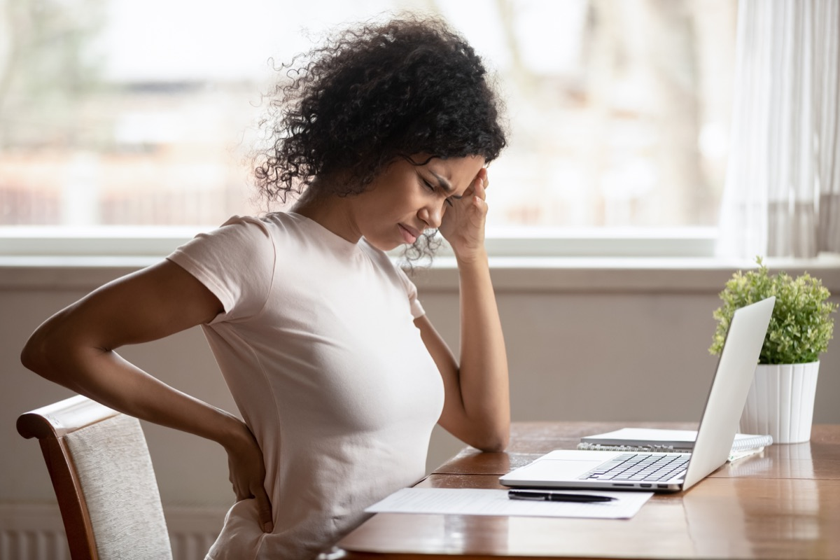 woman looking uncomfortable, hand on back and head, back pain near desk