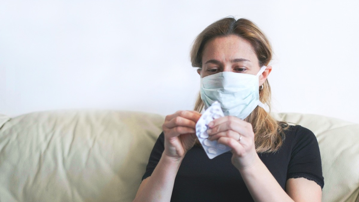 woman wearing mask, sick person opening medicine