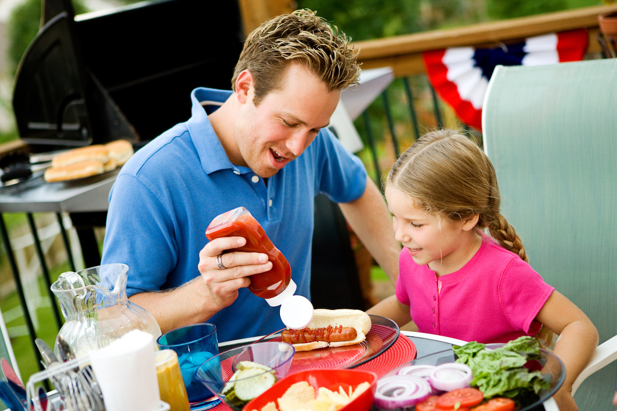 Dad putting ketchup on daughter's hot dog