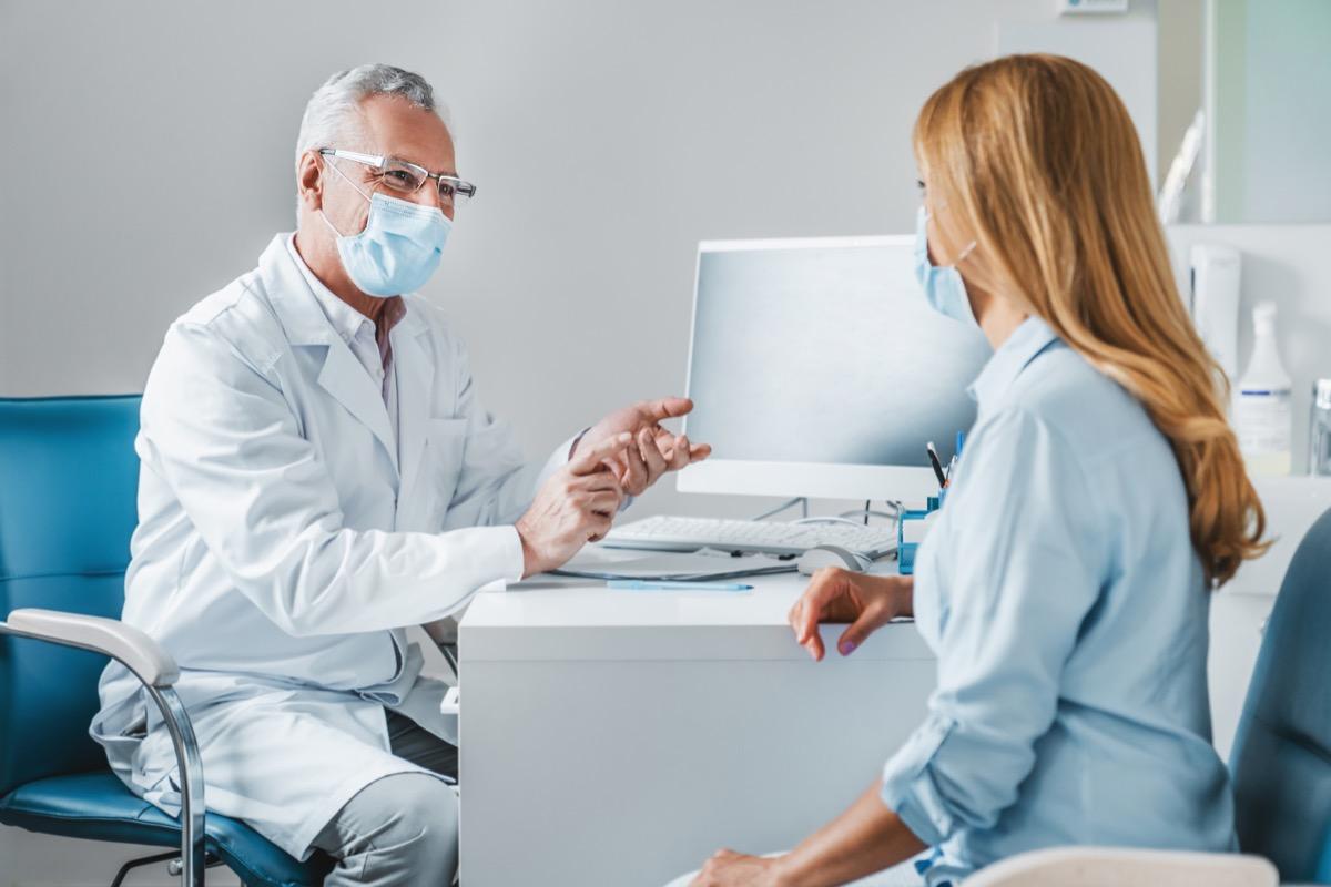 Male doctor speaks to woman patient