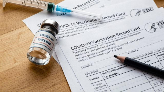 COVID vaccination cards sit on a table top next to a pencil, syringe, and vial of vaccine