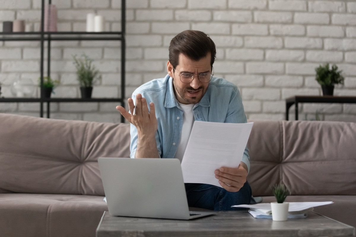 a man looks confused at a paper, computer