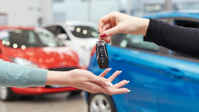 Hands exchanging keys for a new car