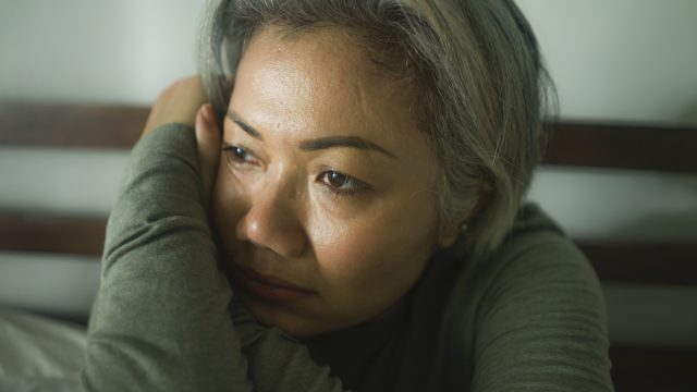 middle aged woman with grey hair feeling sick