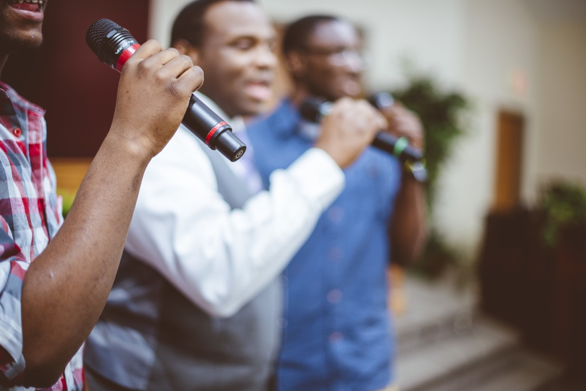 men singing in church with microphones