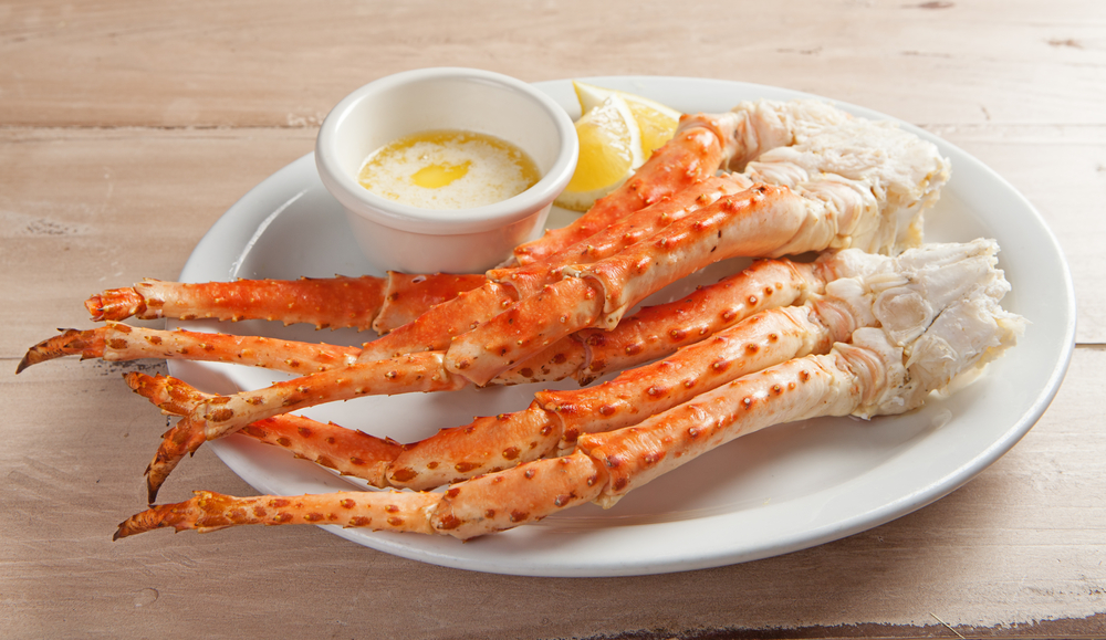 Cooked snow crab legs on a plate with a side of butter