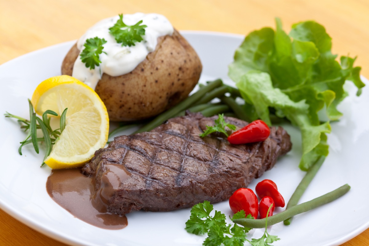 steak and baked potato, lemon, lettuce, place