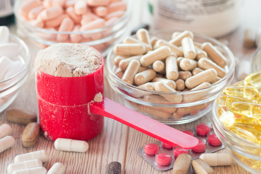 Dietary and athletic supplement pills and powder sitting on a tabletop