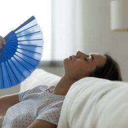 Woman puts head on sofa cushions closed eyes feels sluggish due unbearable heat, waves hand blue fan cool herself