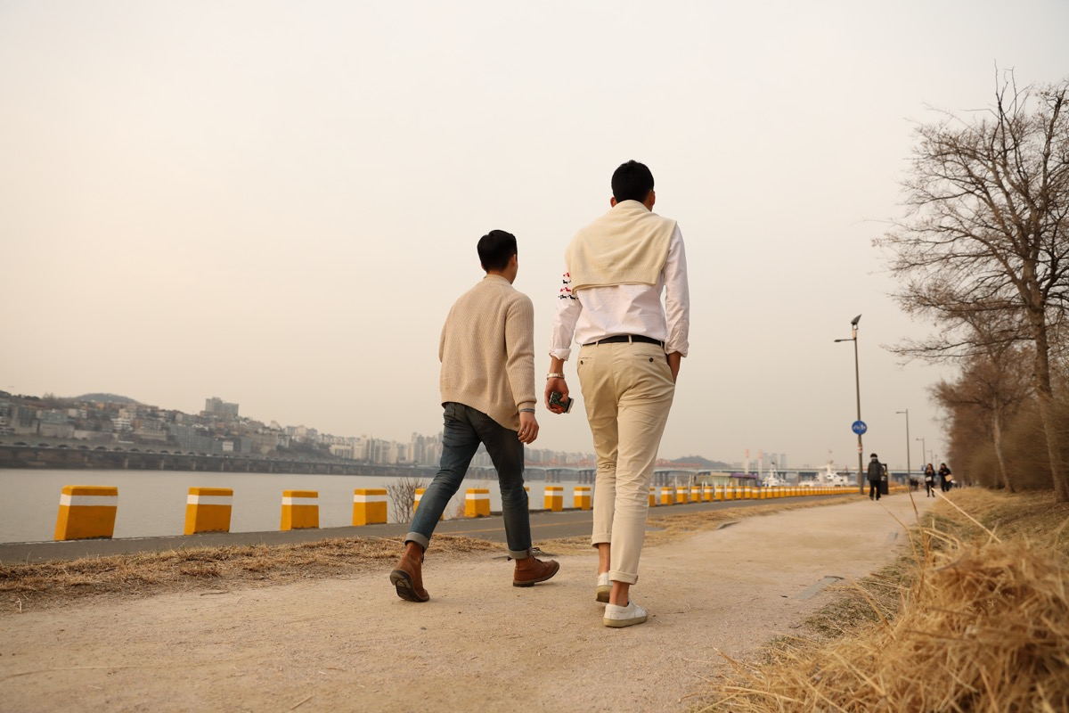 A tall man and a small man are walking in the background of Hannam Bridge and Han river in Sinsa-dong, Gangnam-gu.